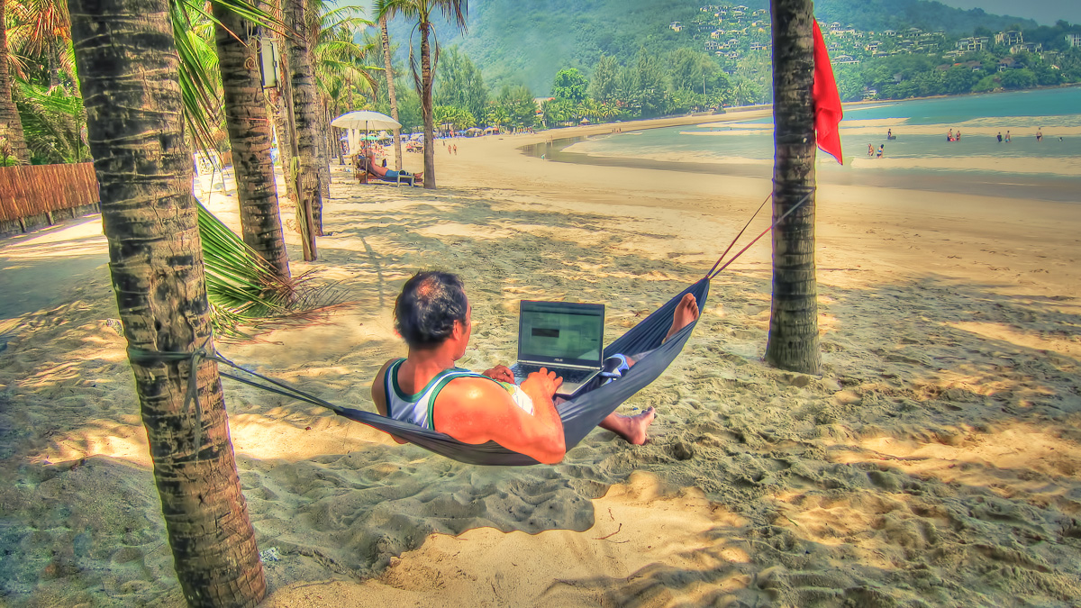 Captain Kimo at the Beach in Phuket Thailand Working on Monthly Newsletter